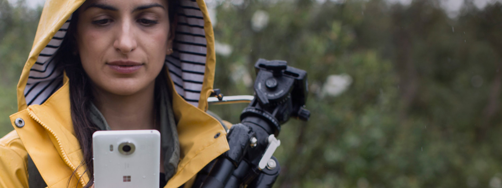Woman wearing raincoat and carrying camera tripod in a wooded area looking at the screen of her Lumia 950