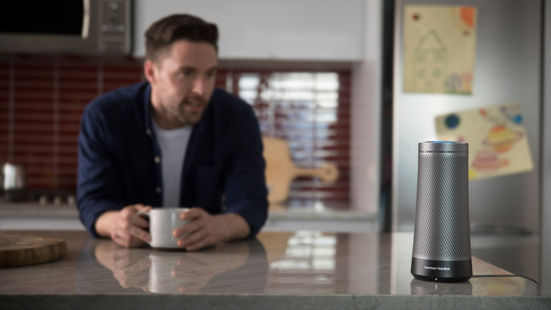 Graphite Invoke speaker on kitchen counter next to man holding coffee cup