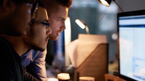 Three men looking at computer screen