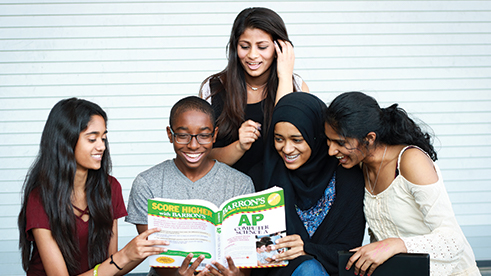 Group of students read AP exam book