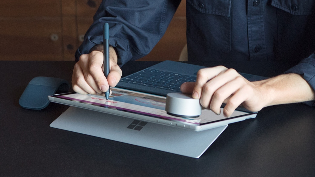 Man drawing on his Surface Pro in Tablet mode with the Surface pen.