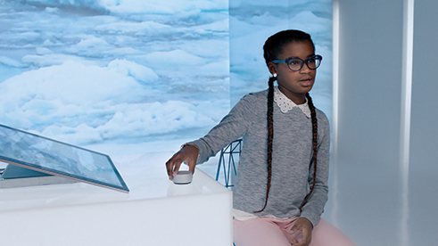 Young girl sitting at a desk using a Microsoft Surface Studio