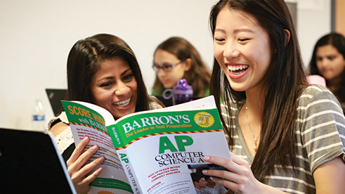 Two girls read an AP computer science text book