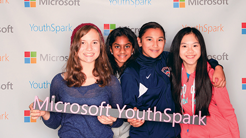 Four young girls holding a Microsoft YouthSpark sign