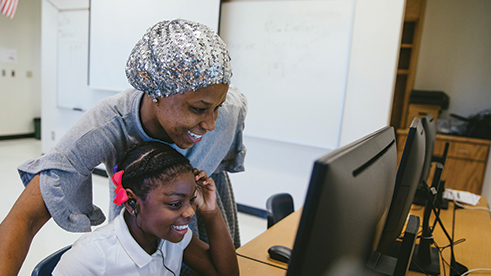 Two young women laughing while looking at a computer screen
