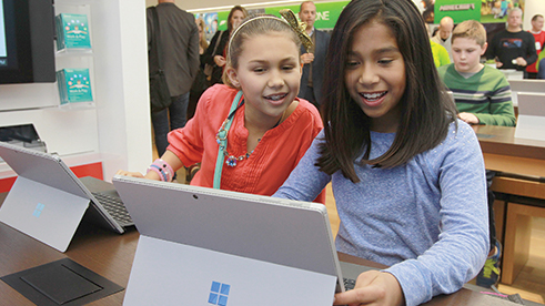 Two young girls coding on Surface laptops