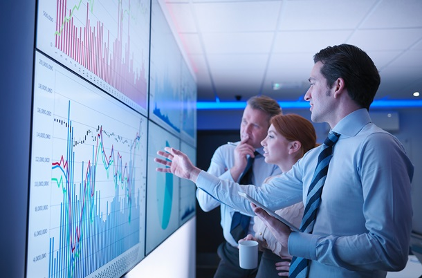 Three people looking at a large screen on the wall displaying charts and graphs.