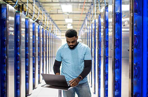 Man standing in a datacenter typing on laptop