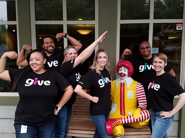 Microsoft employees pose in front of Ronald McDonald House