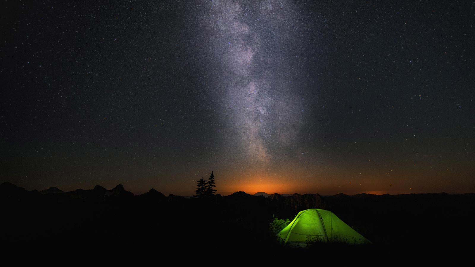 An illuminated tent sits under the milky way.