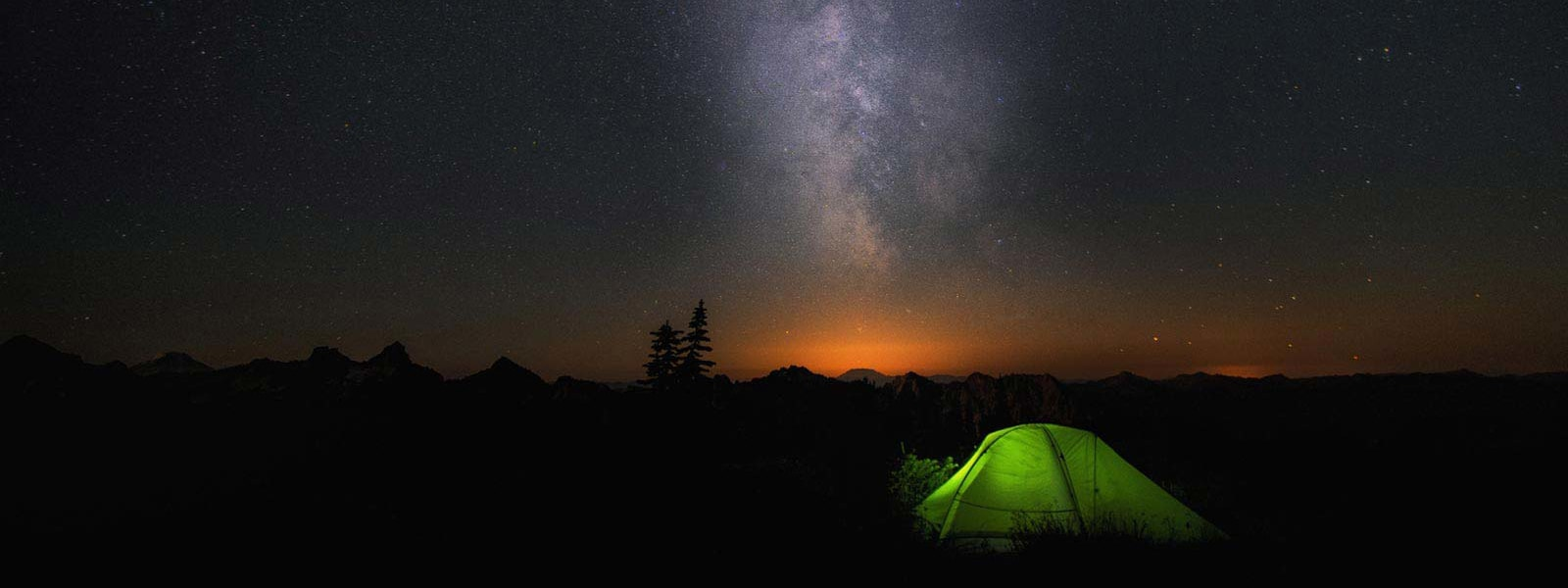 Una tenda verde in una notte scura con la Via lattea all'orizzonte