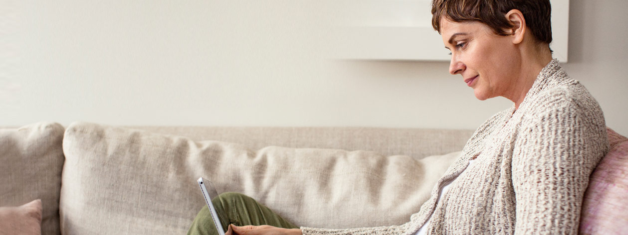 Woman reclining on a couch gazing at a digital device