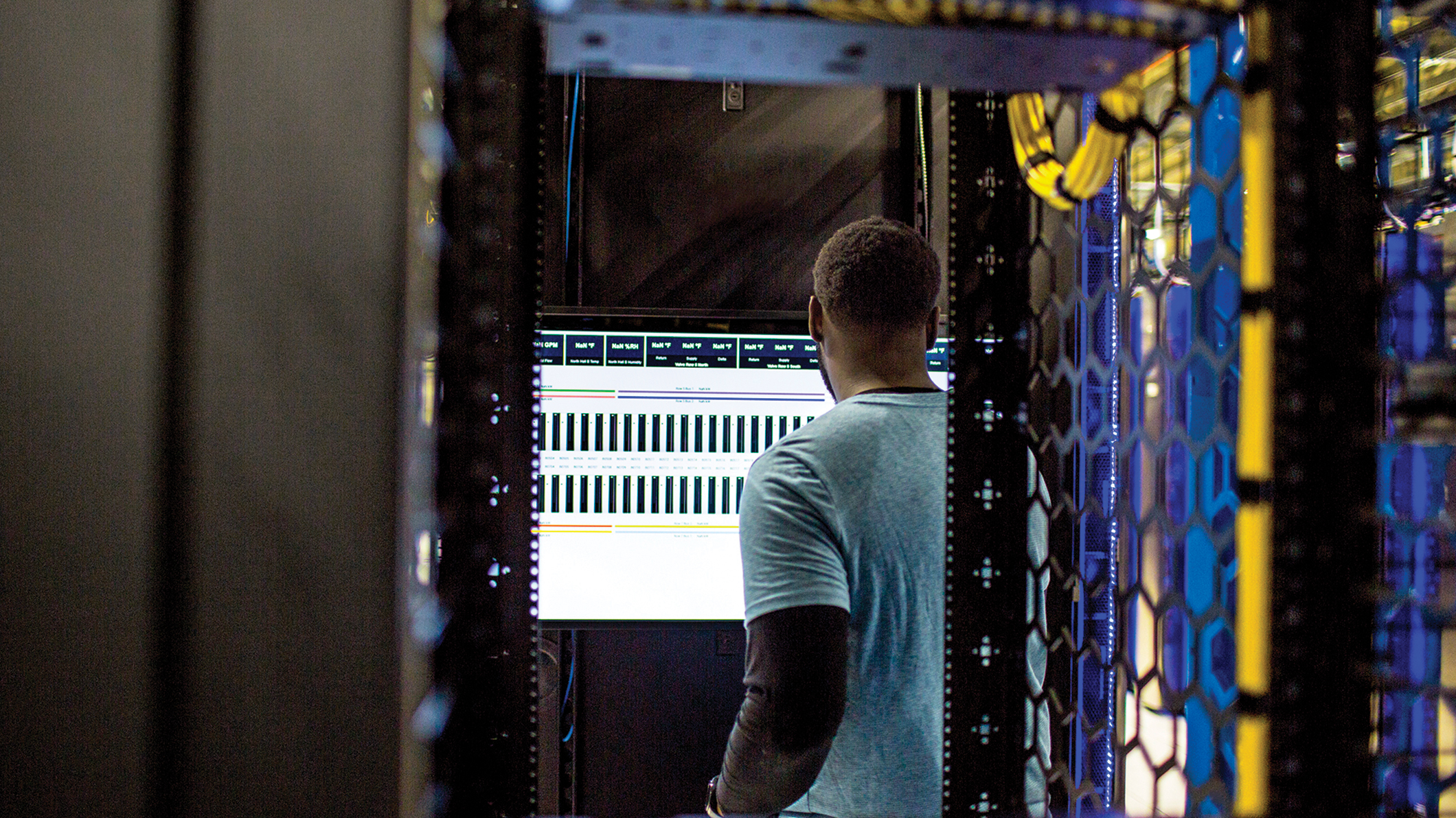 Engineer working on computer in a server room