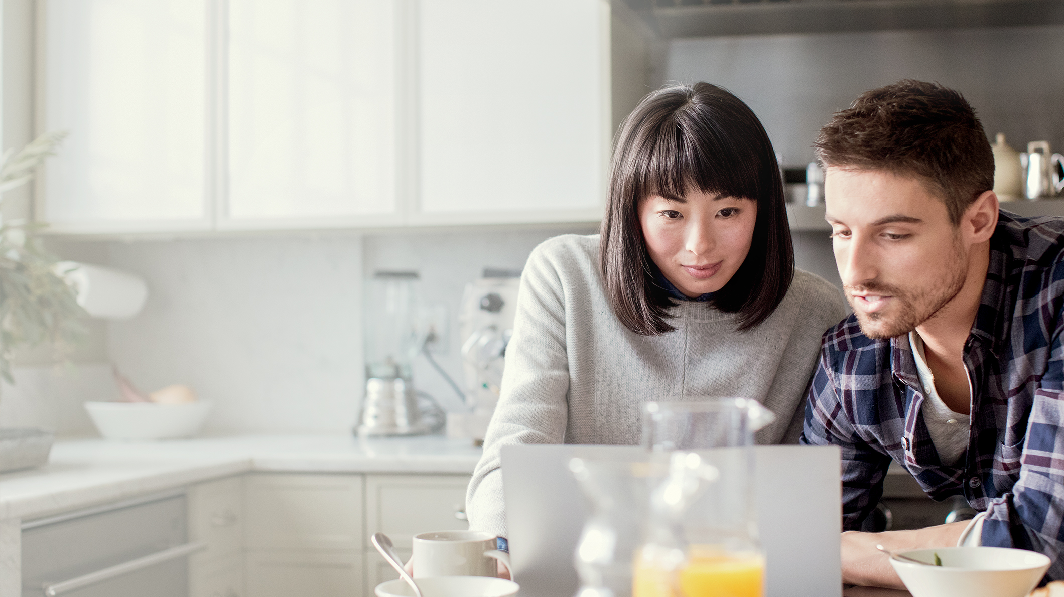 A woman and a man look at a PC screen