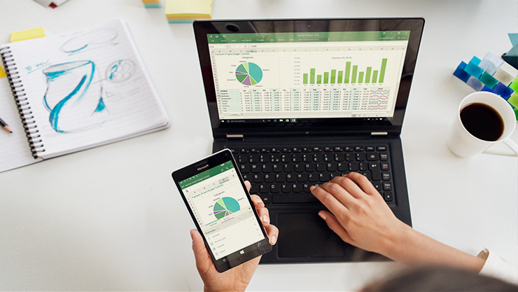 Surface Pro con funda con teclado negra en un escritorio con la mano de una mujer escribiendo en el teclado y con su otra mano sosteniendo un teléfono.