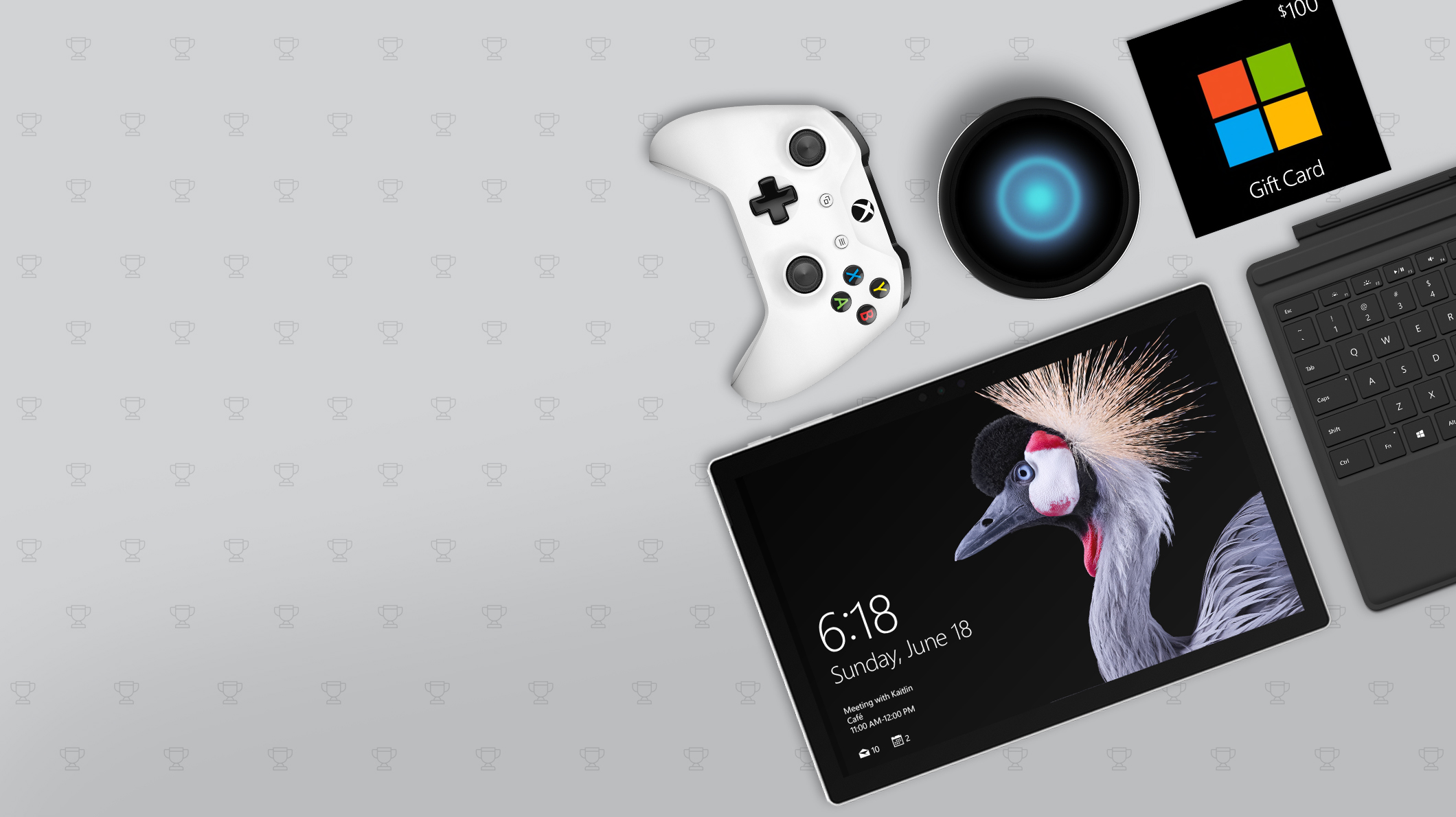 A Surface device, keyboard, Xbox controller, speaker, and Microsoft gift card