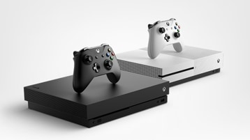 Xbox One X and Xbox One S with controllers sitting next to each other