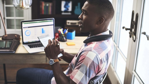 A man sitting at his desk and taking notes on a notepad while listening to music on the JBL Soundgear Wearable Speaker