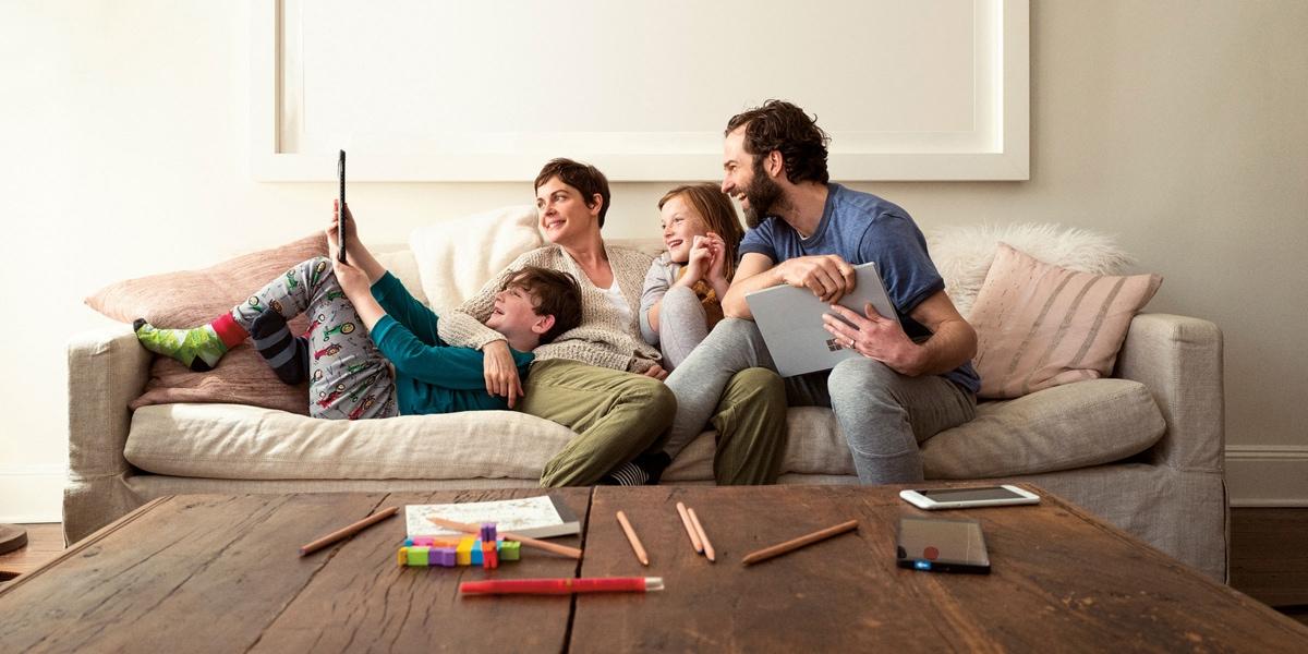 Family of four viewing a screen on a device