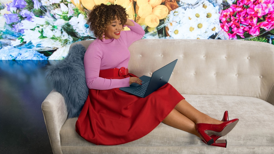 A woman working on her surface laptop on the couch