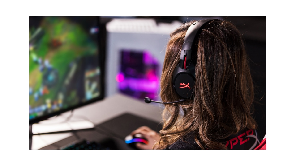 Back view of a woman gaming while wearing Kingston HyperX Cloud Flight headphones.