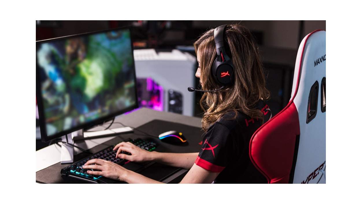 Side view of a woman wearing Kingston HyperX Cloud Flight headphones with microphone while using a gaming PC.