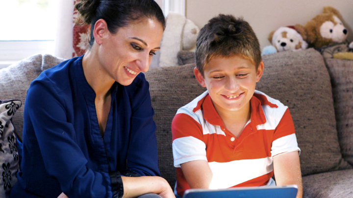 A mother and son smile as they look at a device together.