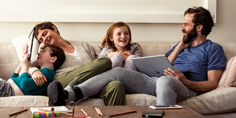 Family sitting together on the couch using a laptop and tablet.