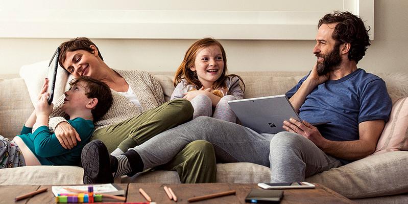 Gia đình ngồi bên nhau trên ghế bằng laptop và máy tính bảng.