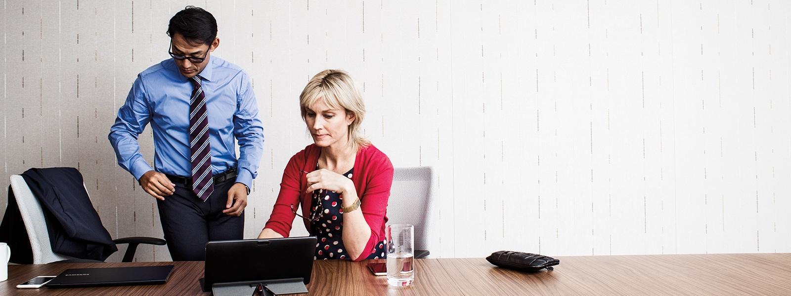 Business man and women talking with two pc's on a desk in an office. | Homme et femmes d'affaires qui discutent et deux PC sur un bureau dans un local.