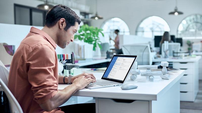 a man in an office using a surface book un homme dans un bureau utilisant