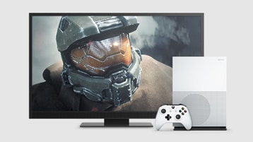 An Xbox One S console and controller, and a big screen playing an action video