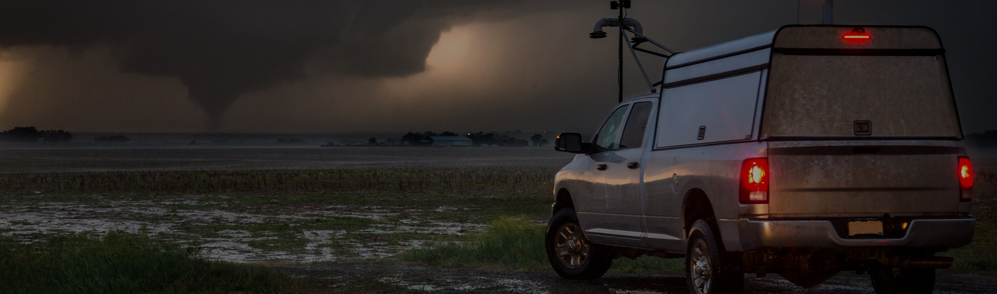 A truck parked on a gravel road as a tornado is approaching in the distance.