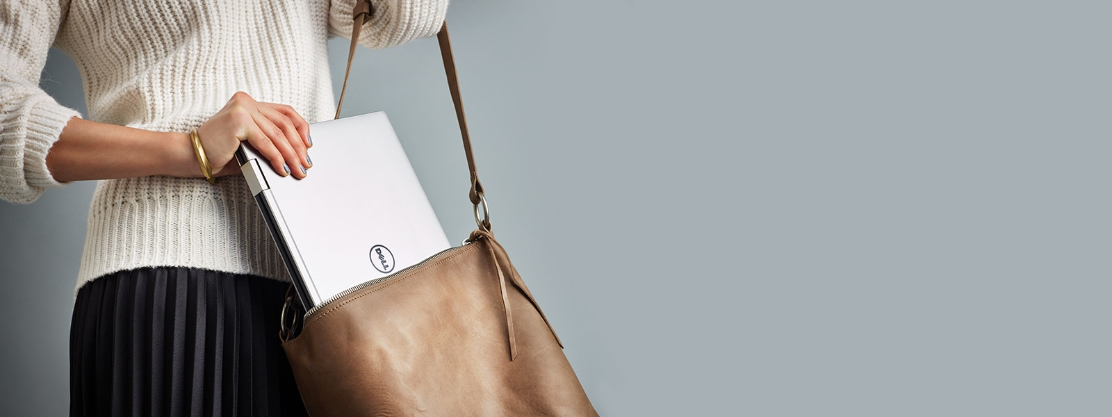 Woman pulling out a Dell XPS laptop from her handbag.