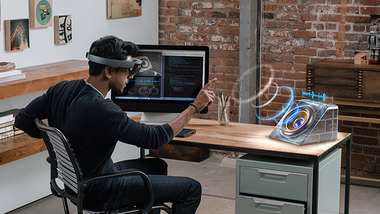 Male using Microsoft Hololens at a desk.