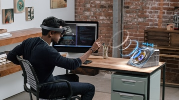 Male using Microsoft Hololens at a desk.