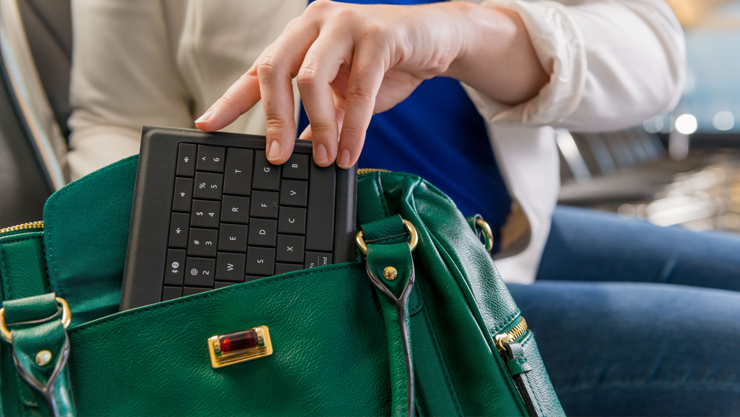 Person taking foldable keyboard out of purse.