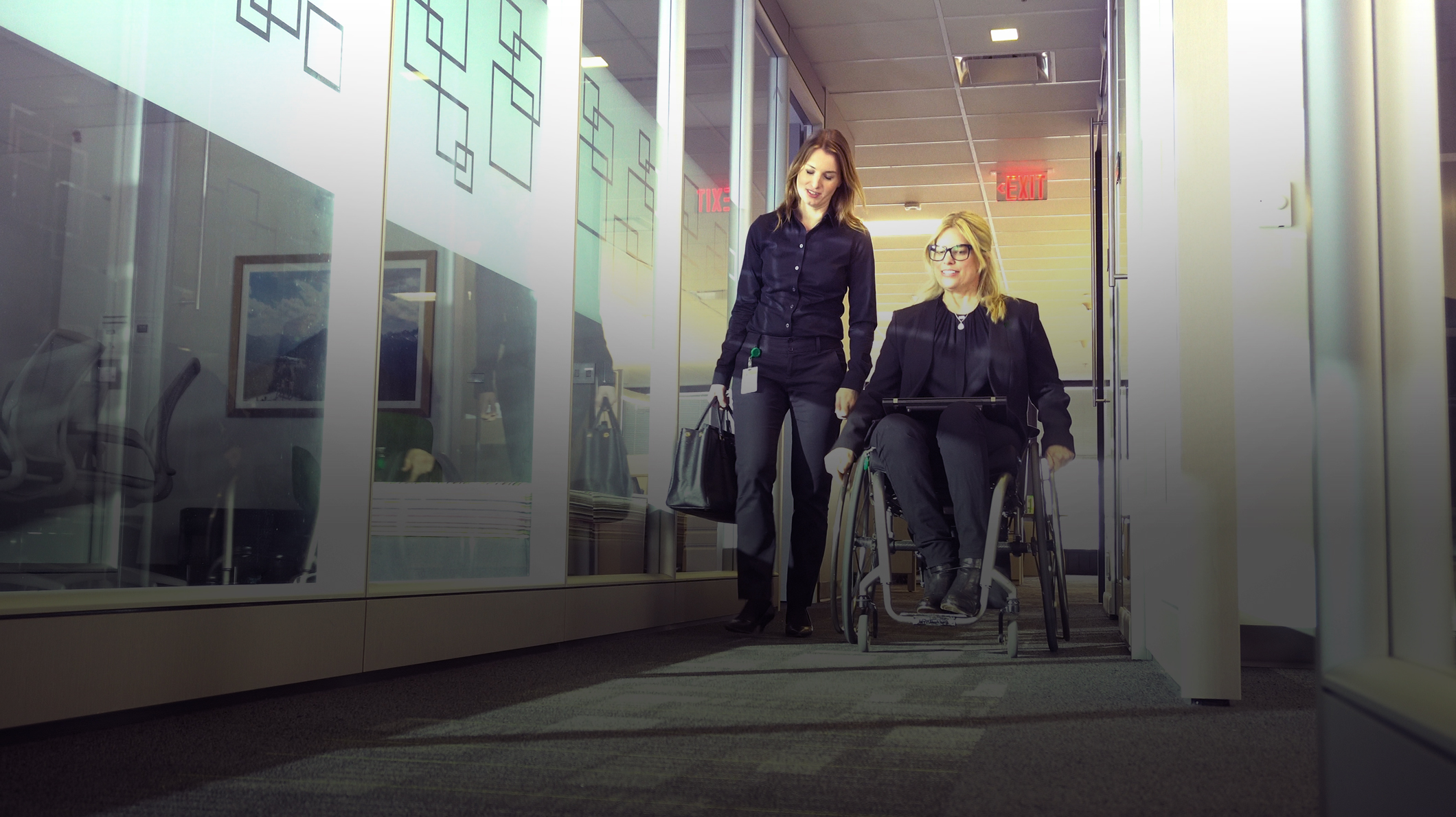 A woman walks alongside a woman in a wheelchair