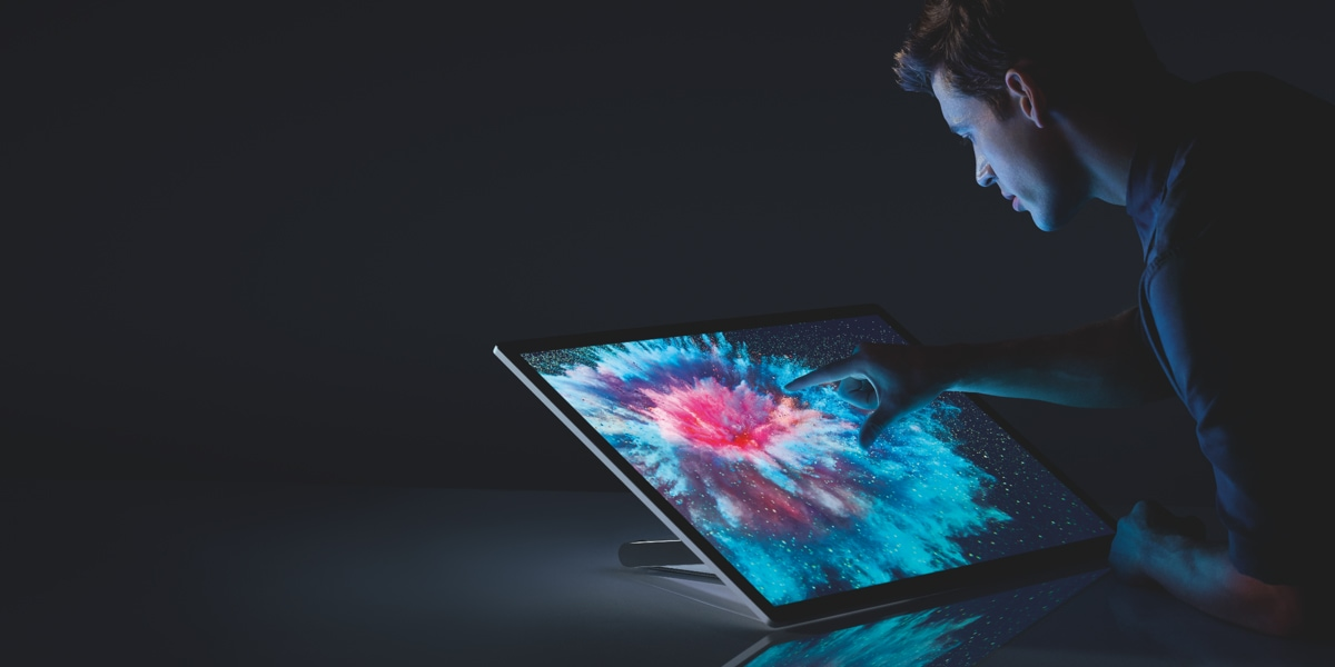 A person interacting with the touch screen on a Surface Studio