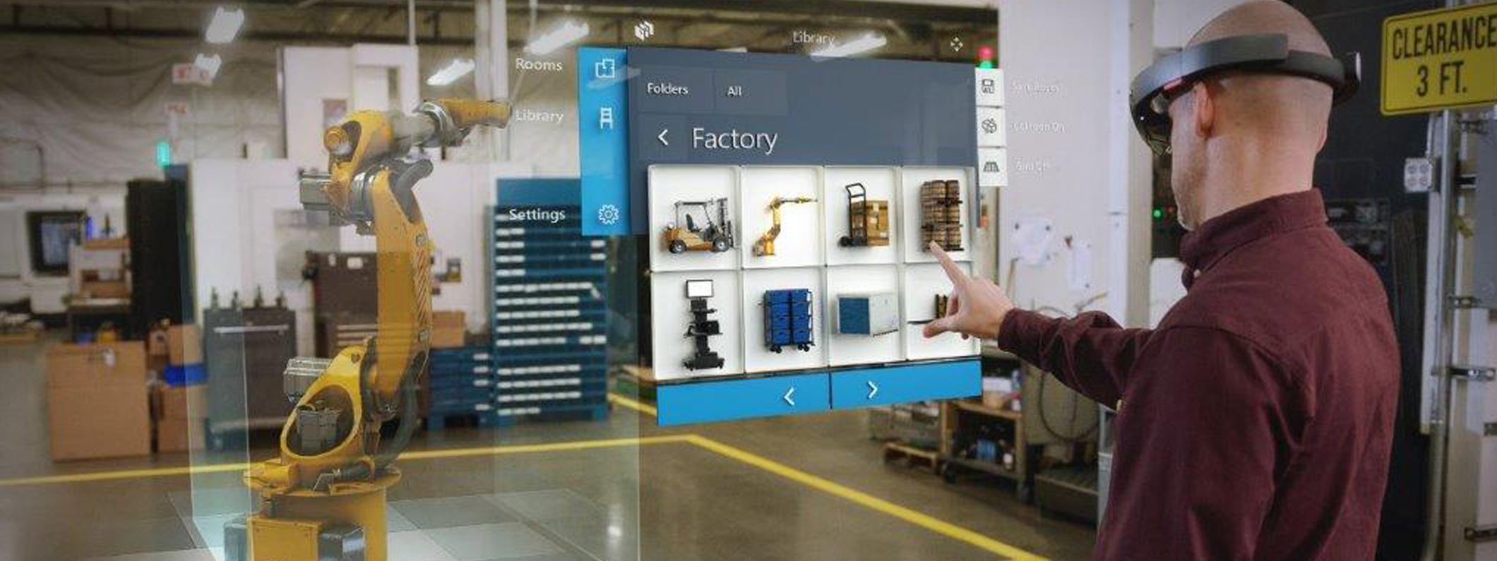 A worker wearing HoloLens uses Microsoft Layout to design space in the real-world, moving and resizing 3D models on the factory floor