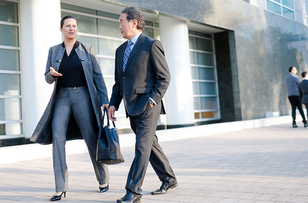 couple in business attire walking past an office building