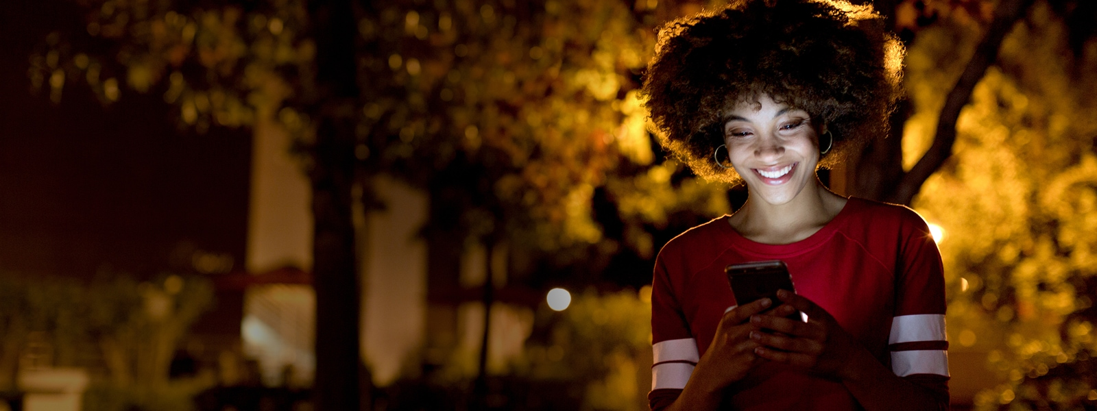 A smiling woman looks at her phone