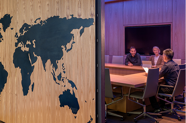 three people sitting in a confernce room with big map of Europe showing on the left wall
