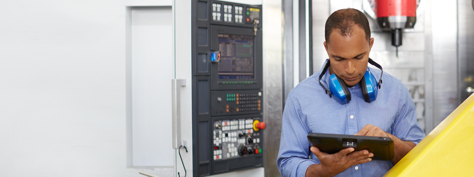 A man with protective headphones works on a tablet.