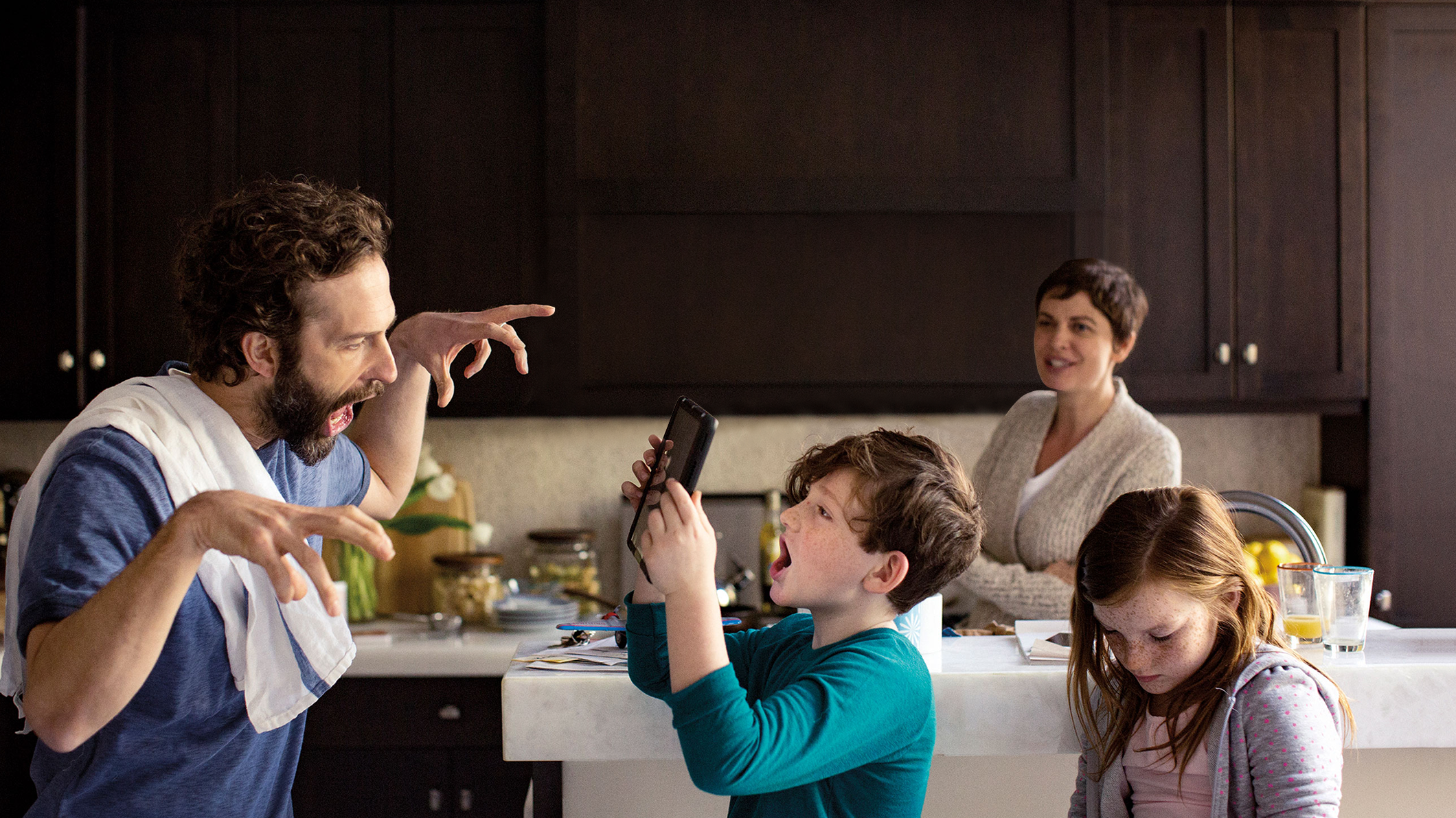 Two kids and their parents gather in a kitchen and take pictures with a tablet
