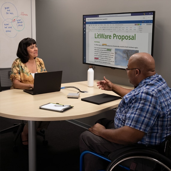 Photograph of two people, one in a wheelchair, talking while in a Microsoft Teams meeting.