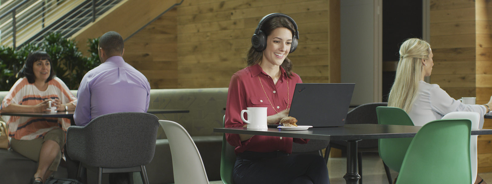 Photo of a woman at a coffee shop using a headset to have a conference call.