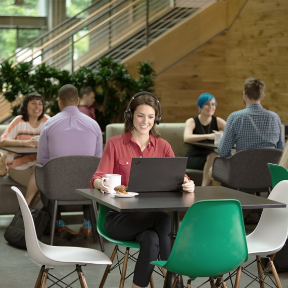 Photograph of a person in a cafeteria with large headphones and a laptop on a video call.