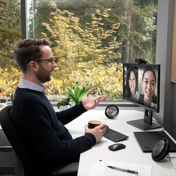 Photograph of a person in a Microsoft Teams meeting on a  desktop hands-free  speaker phones.