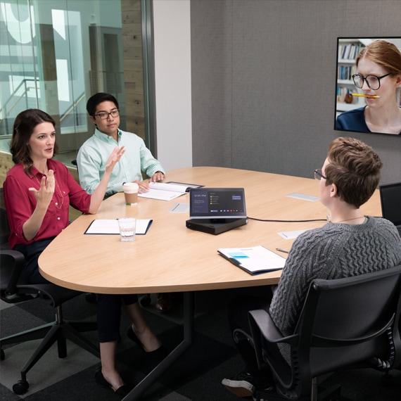 Photograph of people in lively conversation in the meeting room while on a Microsoft Teams call.